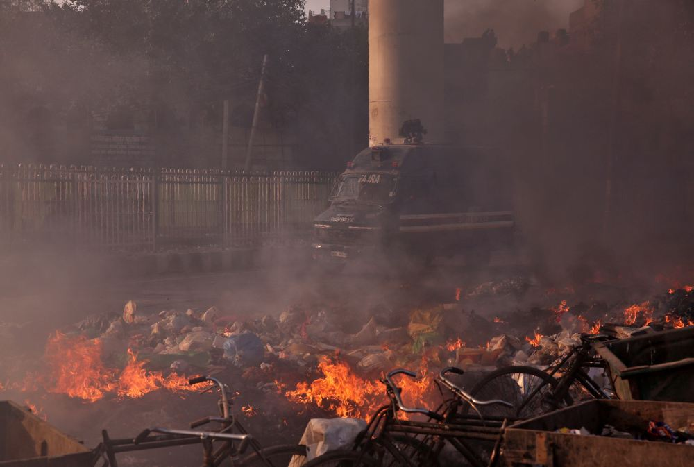 A police vehicle moves past burning debris that was set on fire by demonstrators in a riot affected area after fresh clashes erupted between people demonstrating for and against a new citizenship law in New Delhi February 25, 2020. ― Reuters pic