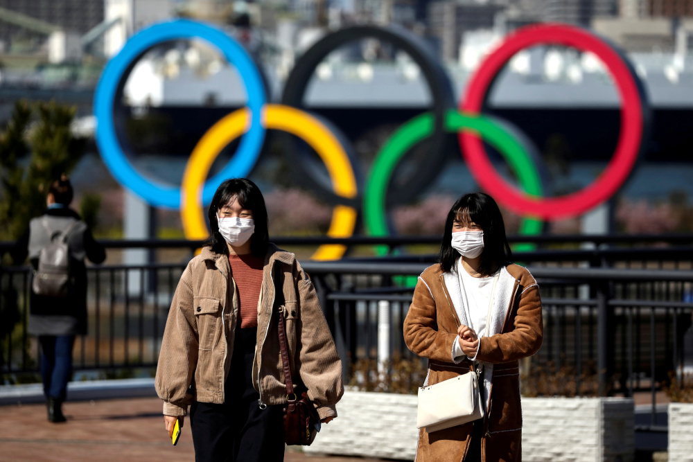 People wearing protective face masks, following an outbreak of the coronavirus, are seen in front of the Giant Olympic rings at the waterfront area at Odaiba Marine Park in Tokyo, Japan, February 27, 2020. — Reuters pic