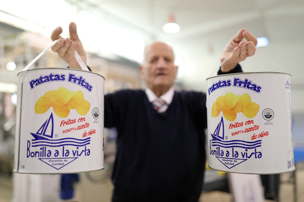 Owner Cesar Bonilla, 87, poses as he holds cans of potato chips during an interview with Reuters inside his Bonilla a la Vista factory in Arteixo, near Coruna, Spain February 17, 2020. — Reuters pic