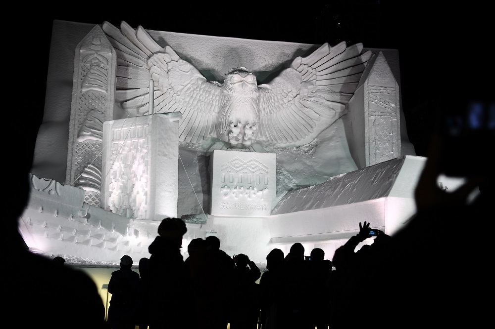 A giant snow sculpture supported by Hokkaido Television Broadcasting representing a 'kotankoro kamuy' (Blakiston's fish owl) watching over the National Ainu Museum, a soon to be opened centre for indigenous northern Japanese Ainu people, is seen after sundown during the Sapporo Snow Festival in Sapporo on February 4, 2020. — AFP pic