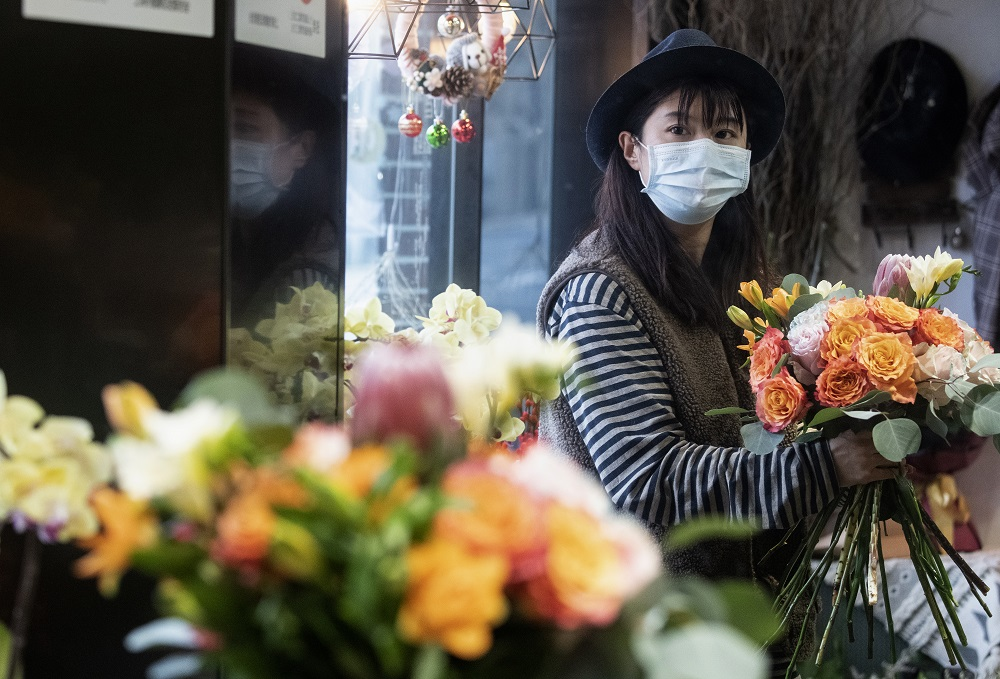 This photo taken on February 12, 2020 shows florist Zhao Yuanyuan wearing a protective face mask as she arranges flowers in her shop in Shanghai ahead of Valentine's Day. — AFP pic