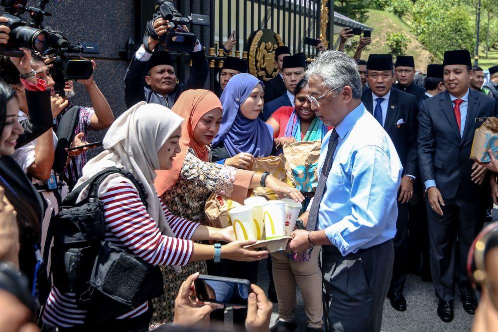 Yang di-Pertuan Agong Al-Sultan Abdullah Ri'ayatuddin Al-Mustafa Billah Shah (centre) distributes food from McDonald's to members of the media at Istana Negara February 25, 2020. ― Picture by Miera Zulyana