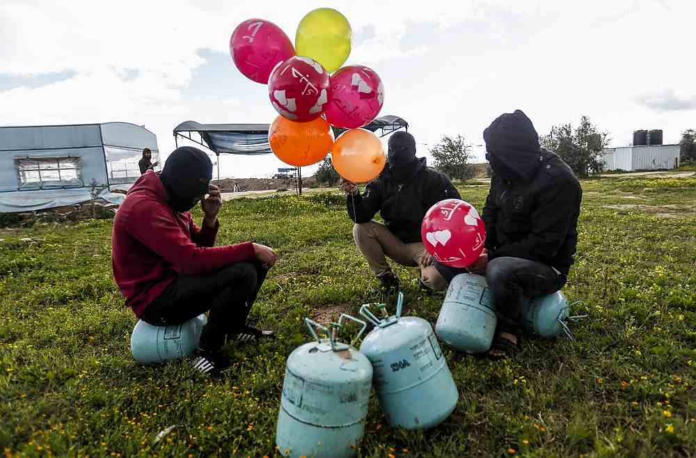 Masked Palestinians prepare to attach balloons to a gas canister before releasing it near Gaza's Bureij refugee camp, along the Israel-Gaza border fence February 10, 2020. — AFP