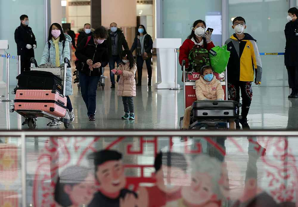 Travellers wearing face masks arrive at the Beijing Capital International Airport as the country is hit by an outbreak of the new coronavirus February 2, 2020. — China Daily pic via Reuter