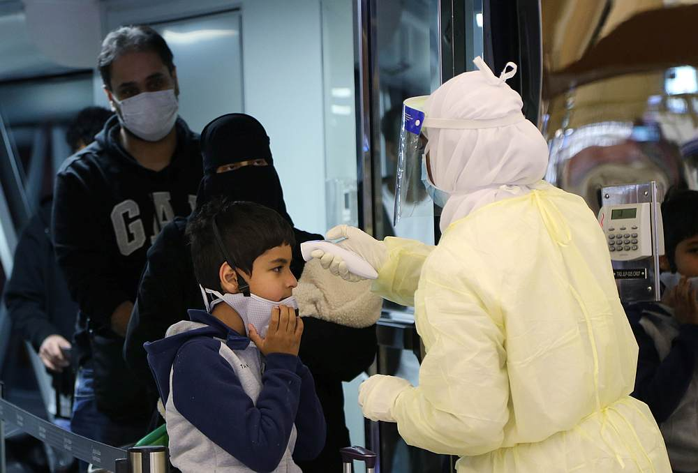 Passengers coming from China wearing masks are checked by Saudi Health Ministry employees upon their arrival at King Khalid International Airport, in Riyadh, Saudi Arabia January 29, 2020. — Reuters pic