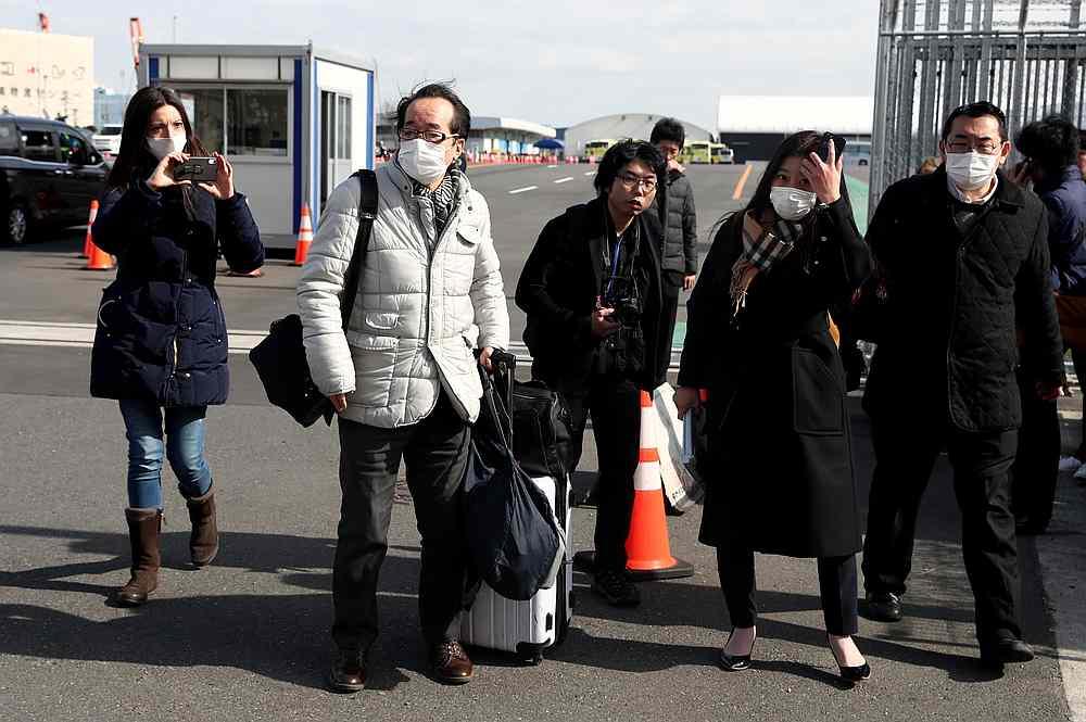 Passengers wearing face masks walk out from the cruise ship Diamond Princess at Daikoku Pier Cruise Terminal in Yokohama, south of Tokyo, Japan February 19, 2020. — Reuters pic