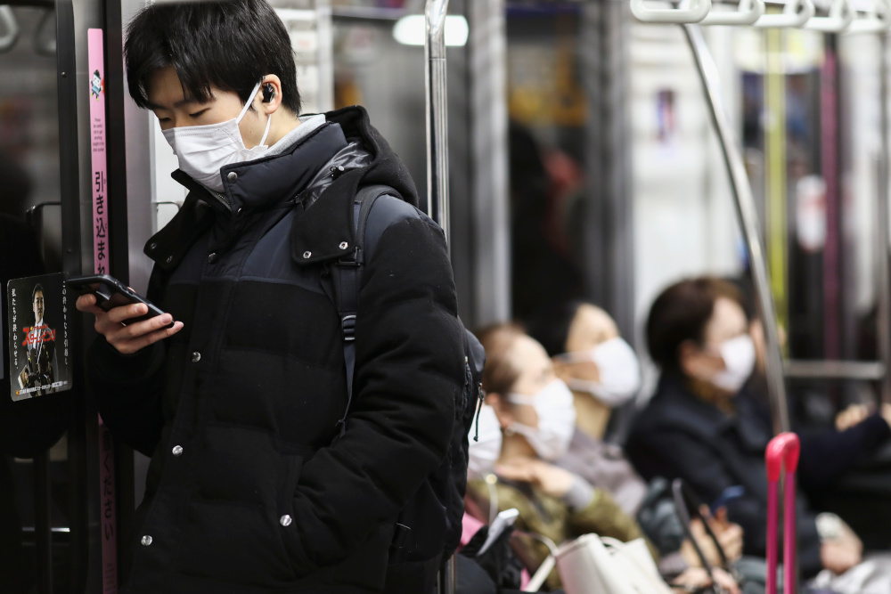 Passengers wearing protective face masks are seen as they ride on a train in Tokyo, Japan, February 14, 2020. — Reuters pic