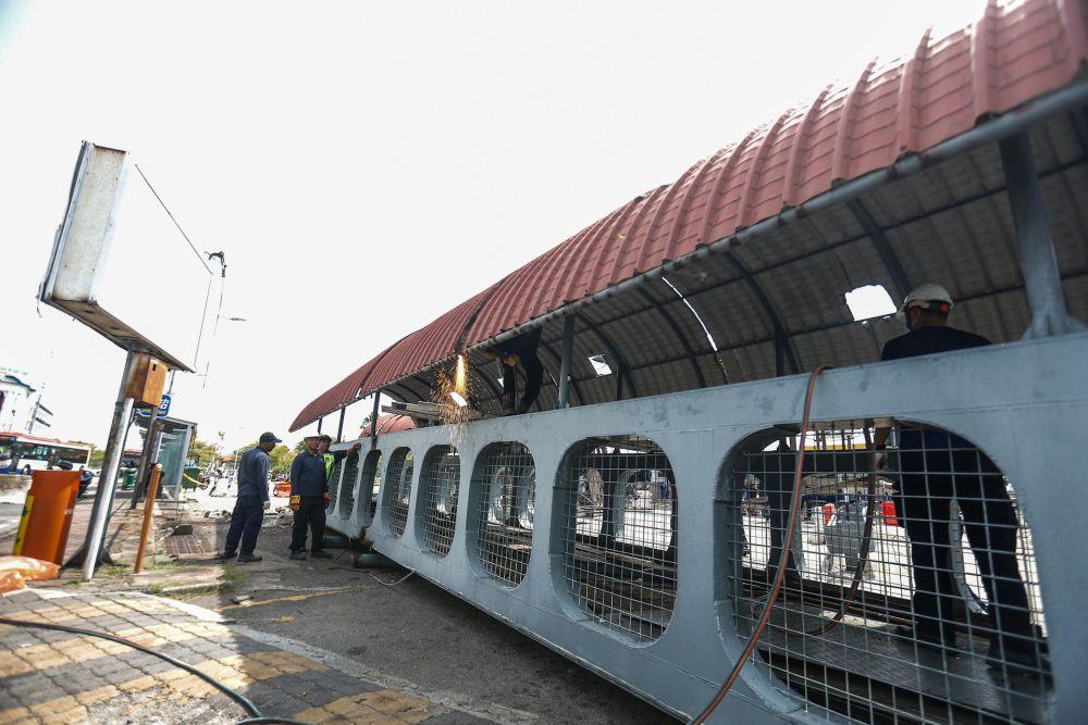Penang Island Municipal Council staff dismantle the damaged pedestrian bridge at Weld Quay February 6, 2020. — Picture by Sayuti Zainudin