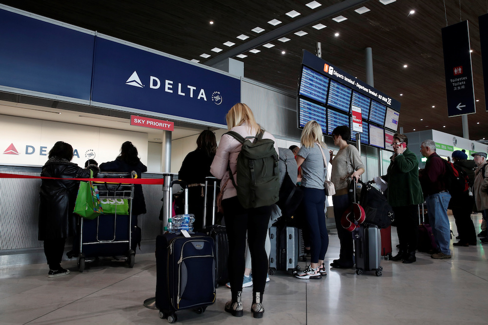 People line up at the Delta Air Lines ticketing desk inside Terminal 2E at Paris Charles de Gaulle airport in Roissy, after the US banned travel from Europe, as France grapples with an outbreak of Covid-19, March 12, 2020. — Reuters pic