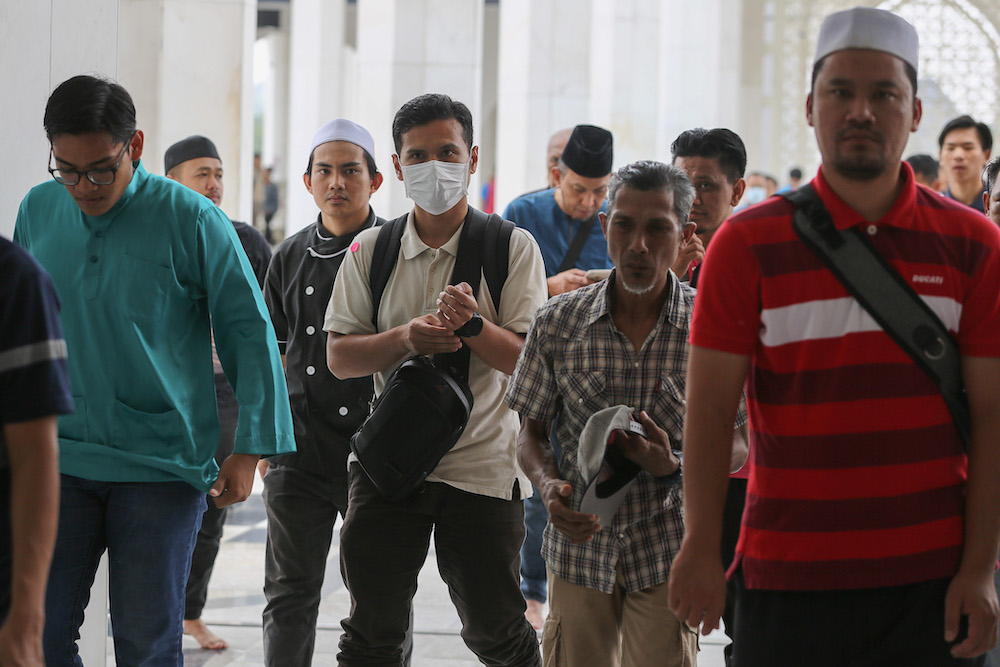 A man wears a protective mask as he attends Friday prayers at Sultan Salahuddin Abdul Aziz Shah Mosque in Shah Alam March 13, 2020. Pakatan Harapan's Secretarial Council has called upon the Health Ministry to prioritise human resources as well as critical medical and protective equipment for the next wave of Covid-19 infections. — Picture by Yusof Mat Isa