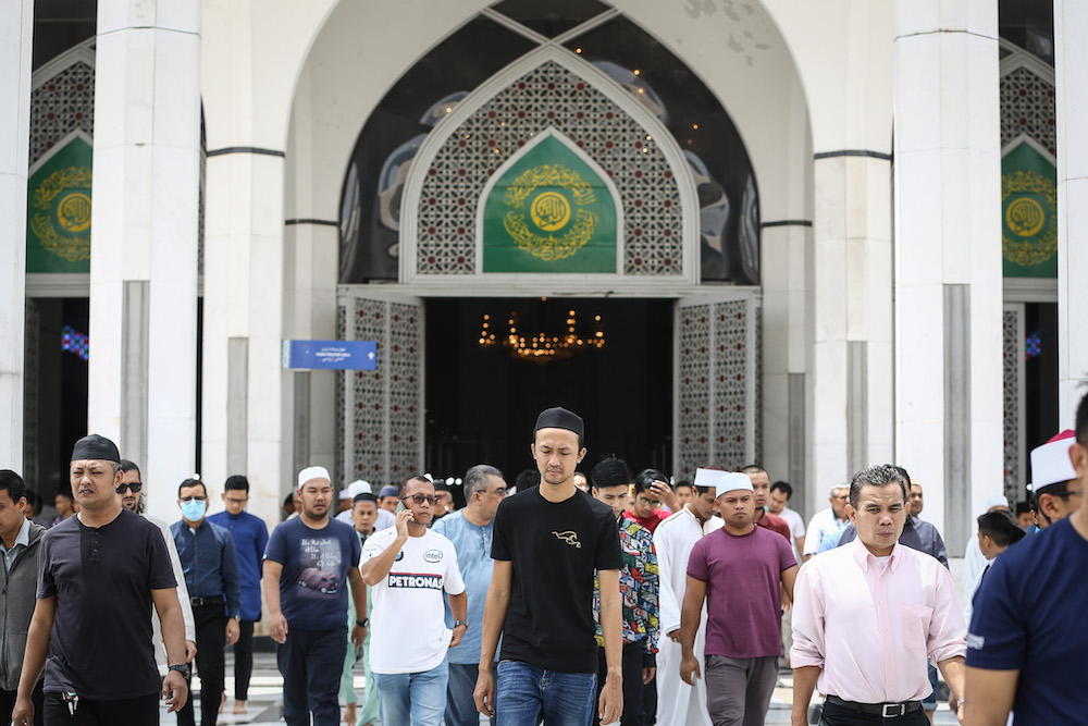 Worshippers leave after Friday prayers at Sultan Salahuddin Abdul Aziz Shah Mosque in Shah Alam March 13, 2020. — Picture by Yusof Mat Isa