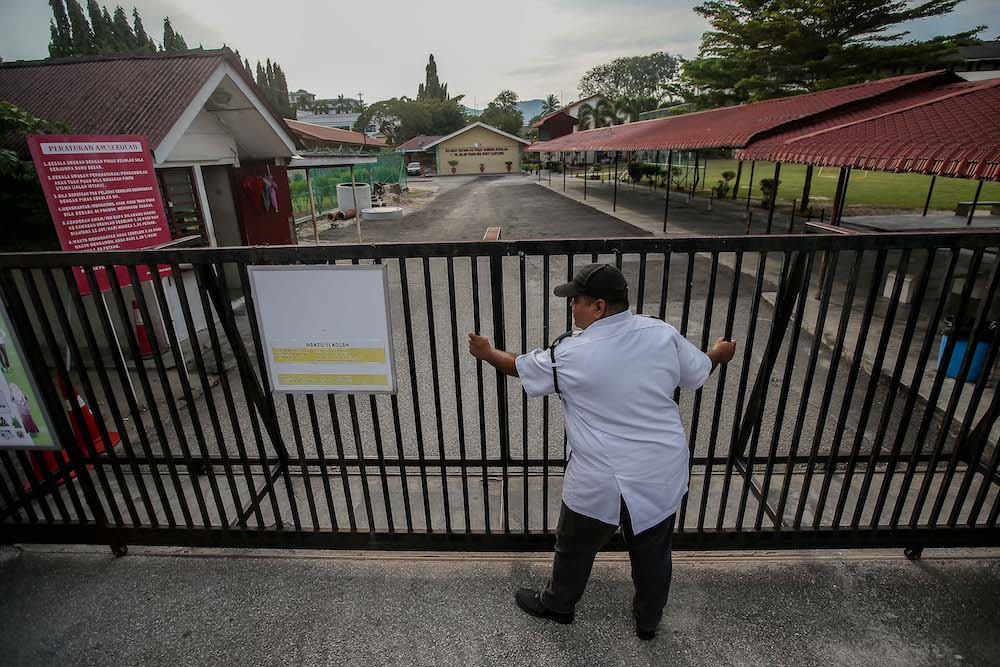 A security guard at SK Panglima Bukit Gantang Ipoh closes the school gate amid the movement control order March 17, 2020. — Picture by Farhan Najib