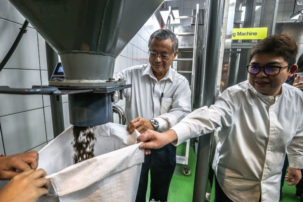General Manager of 1 Utama, Samantha Lee, and Director of 1 Utama, Tan Sri Datuk Teo Chiang Kok,   showing the end process of the food waste that has turned into fertilizer. — Picture by Firdaus Latif