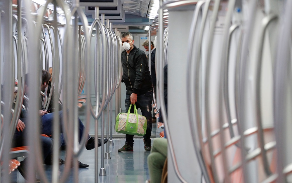 A man wearing a protective face mask stands inside a metro train, on the third day of an unprecedented lockdown across of all Italy imposed to slow the outbreak of coronavirus, in Rome March 12, 2020. — Reuters pic