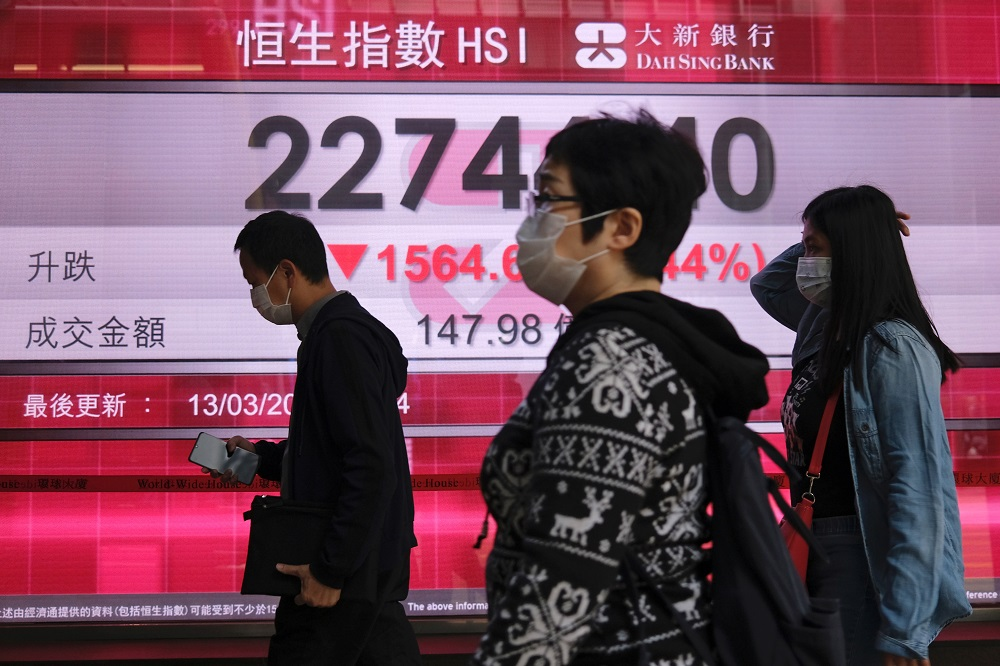 People wear protective masks as they walk past a panel displaying the Hang Seng Index during morning trading, following the outbreak of the new coronavirus, in Hong Kong March 13, 2020. — Reuters pic