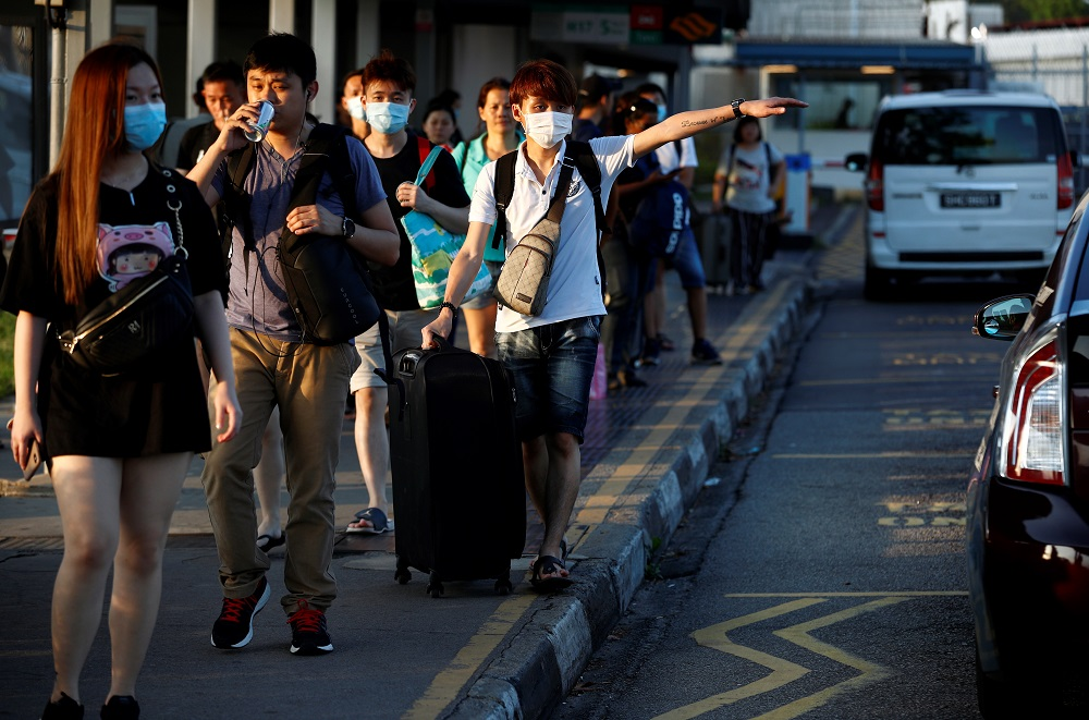 Commuters leave the Woodlands Causeway across to Singapore from Johor, hours before Malaysia imposes a movement control order on travel due to the coronavirus outbreak, in Singapore March 17, 2020. — Reuters pic