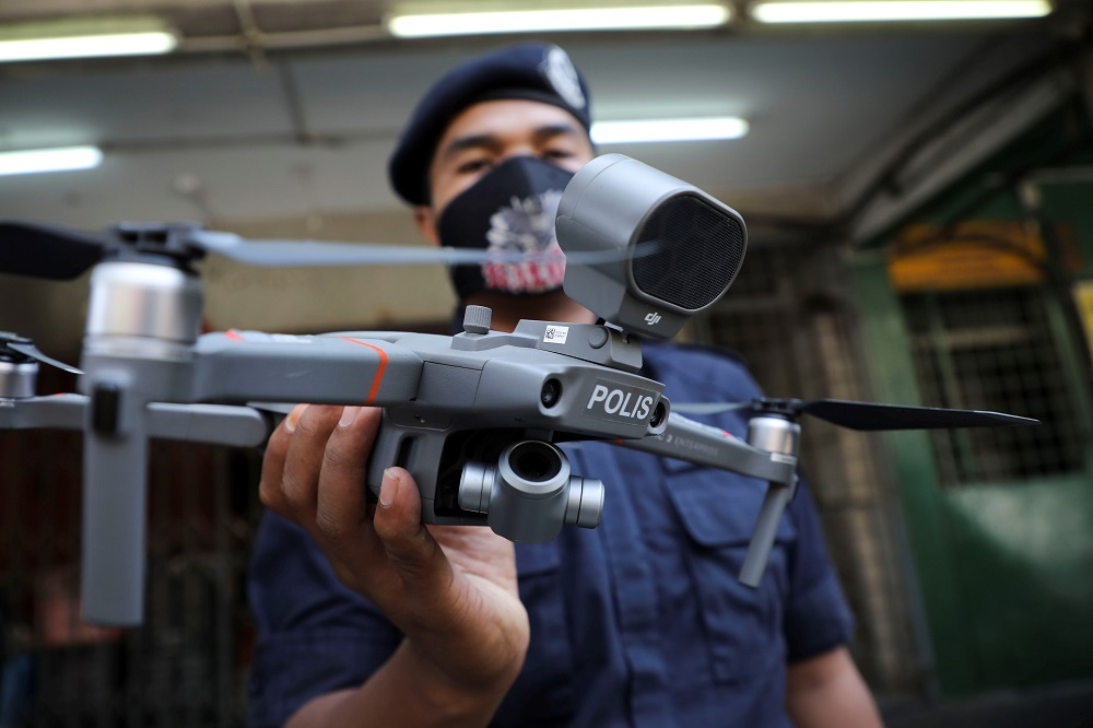 A police officer holds a drone, which is used by Malaysian police to remind citizens to stay at home during the movement control order due to the outbreak of the coronavirus disease in Kuala Lumpur March 24, 2020. — Reuters pic