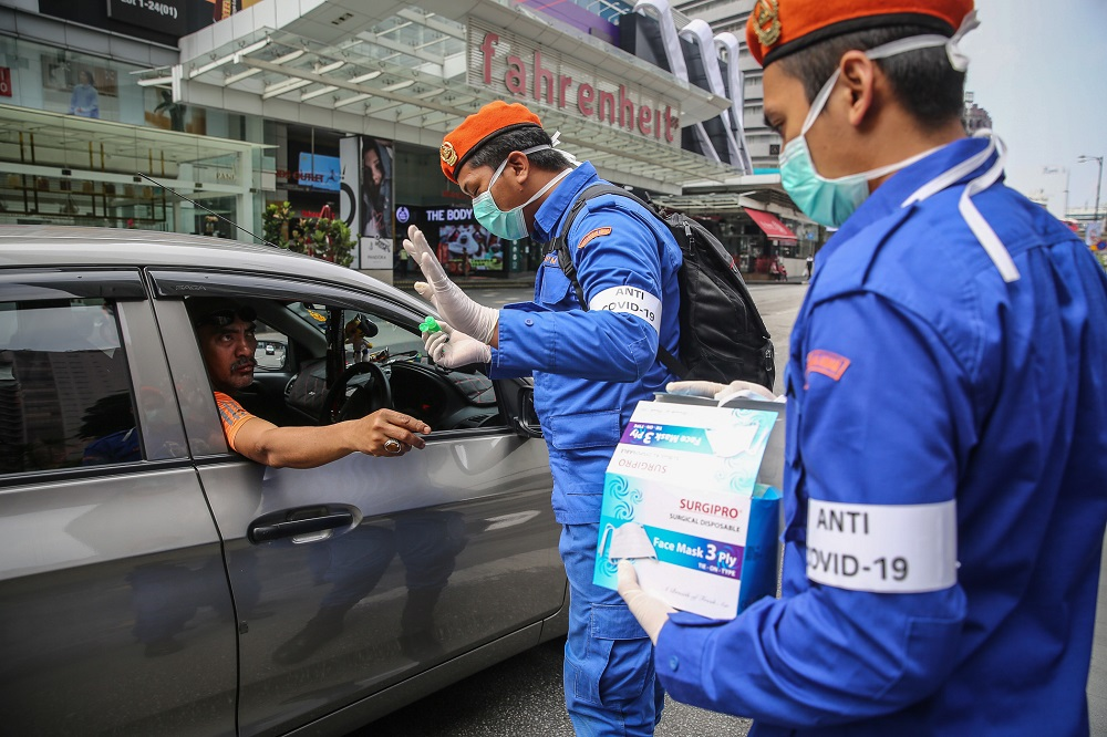 Malaysia Civil Defence Force personnel distributing protective face masks to the public in Kuala Lumpur March 21, 2020. — Picture by Yusof Mat Isa