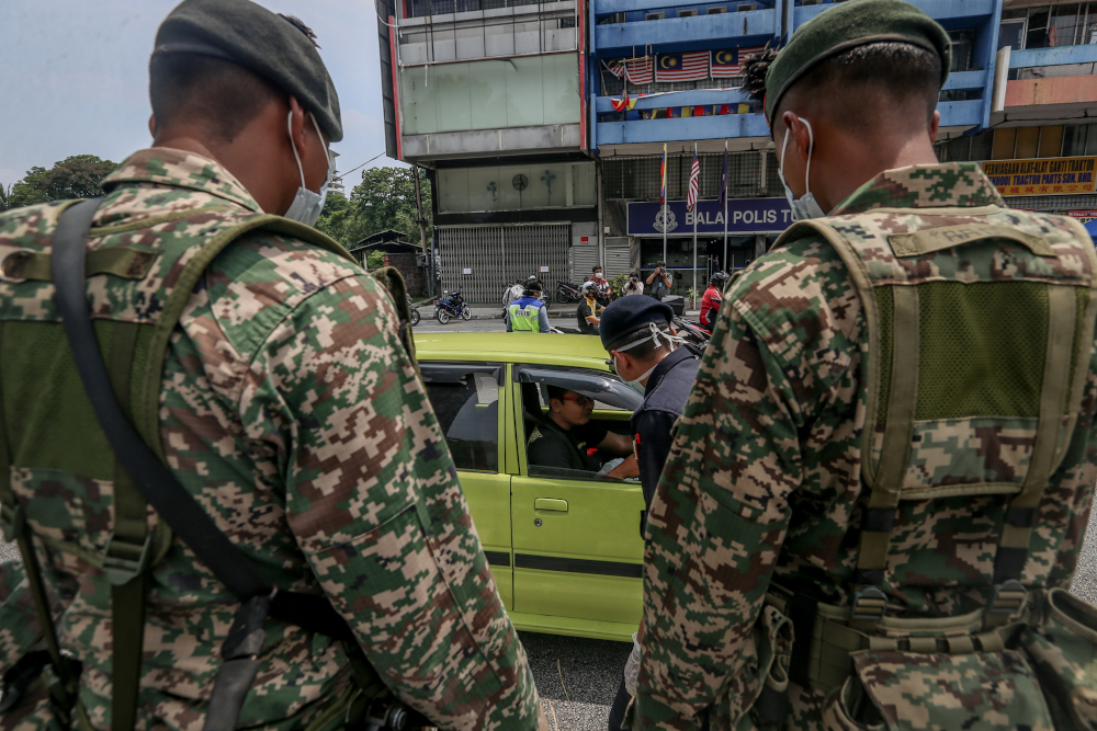 Soldiers and police officers conducting checks at a roadblock on day five of the movement control order (MCO) at Jalan Loke Yew in Kuala Lumpur March 22, 2020. The Eastern Sabah Security Command is constantly working with Philippine security forces to tighten security and curb cross-boundary criminal threats, especially during the MCO. — Picture by Firdaus Latif