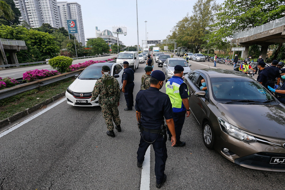 Several Malaysian Armed Forces personnel are seen assisting the police at one of the roadblocks to help maintain the movement control order at Tun Dr Lim Choong Eu Highway in Penang March 22, 2020. — Picture by Sayuti Zainudin
