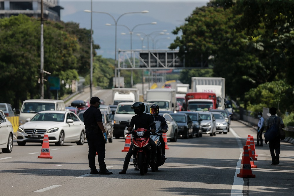Police personnel are seen at a roadblock at Jalan Kuching in Kuala Lumpur March 28, 2020. PLUS expects more than 300,000 'Gerak Malaysia' applicants for interstate travel to be moving across the country, including its highway network from tomorrow until Sunday. — Picture by Ahmad Zamzahuri