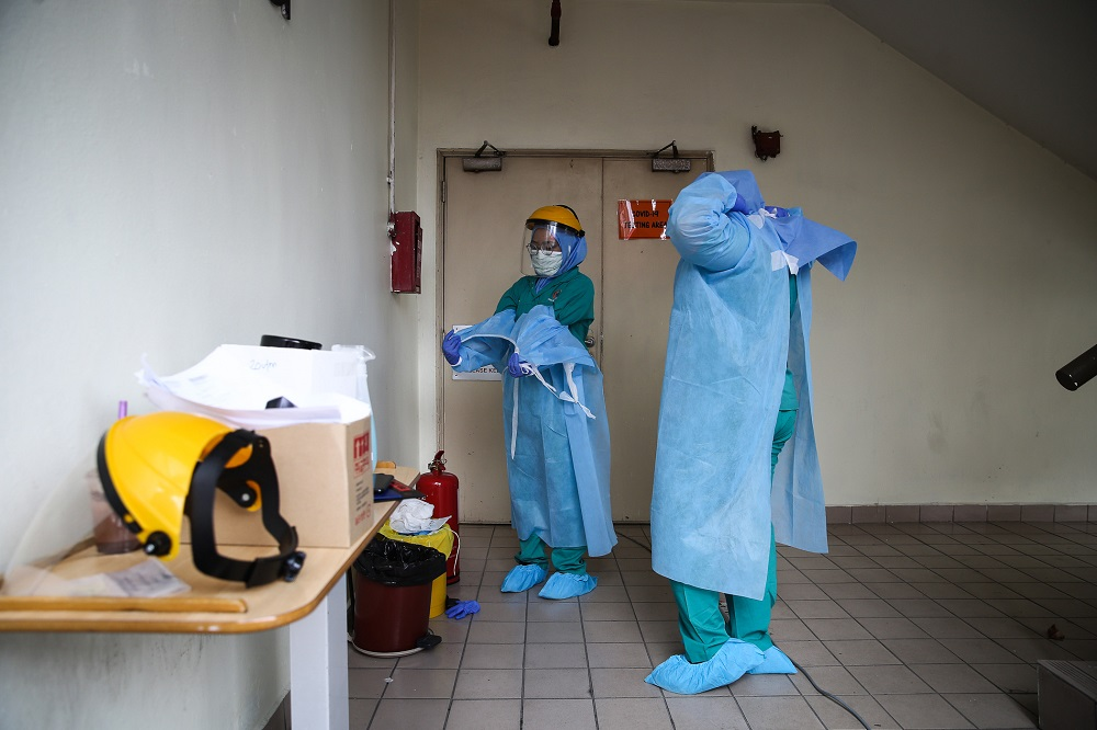 Health workers in protective suits are seen at a drive-through testing site for Covid-19 at KPJ Damansara Specialist Hospital in Petaling Jaya March 28, 2020. — Picture by Yusof Mat Isa