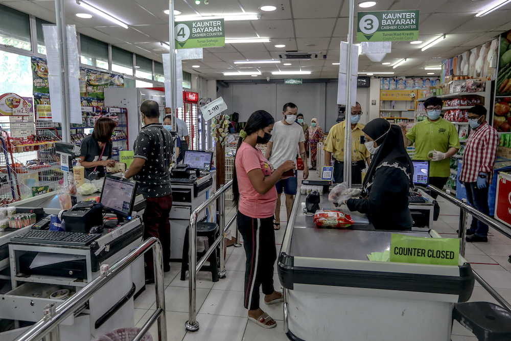 Shoppers stand at a distance from each other in a grocery store store in Cheras March 22, 2020. — Picture by Firdaus Latif