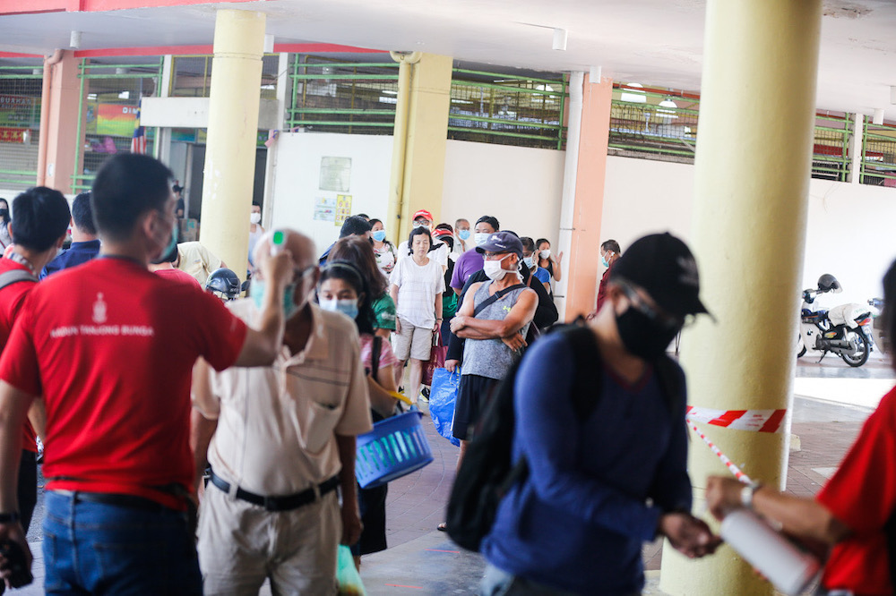 Members of the public are seen adhering to 'social distancing' guidelines as they buy groceries at Tanjung Bungah wet market, March 22, 2020. Picture by Sayuti Zainudin