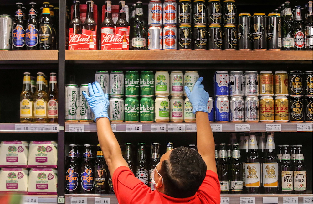 A Jaya Grocer staff is pictured arranging cans of beer in Ipoh. — Picture by Farhan Najib