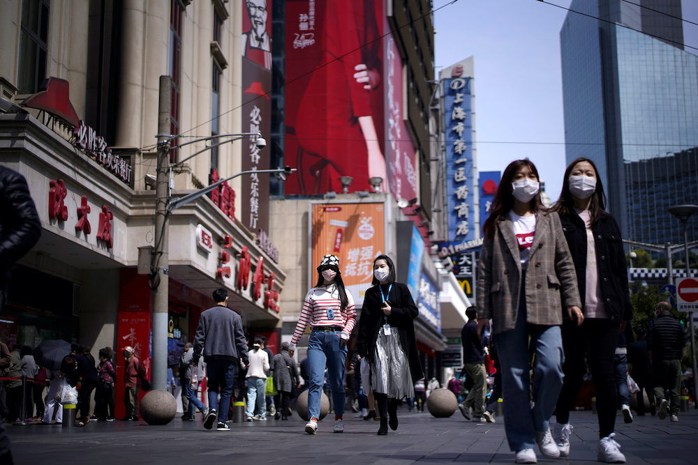 People wear masks at a main shopping area after the city's emergency alert level for coronavirus disease (Covid-19) was downgraded, in Shanghai March 23, 2020. — Reuters pic