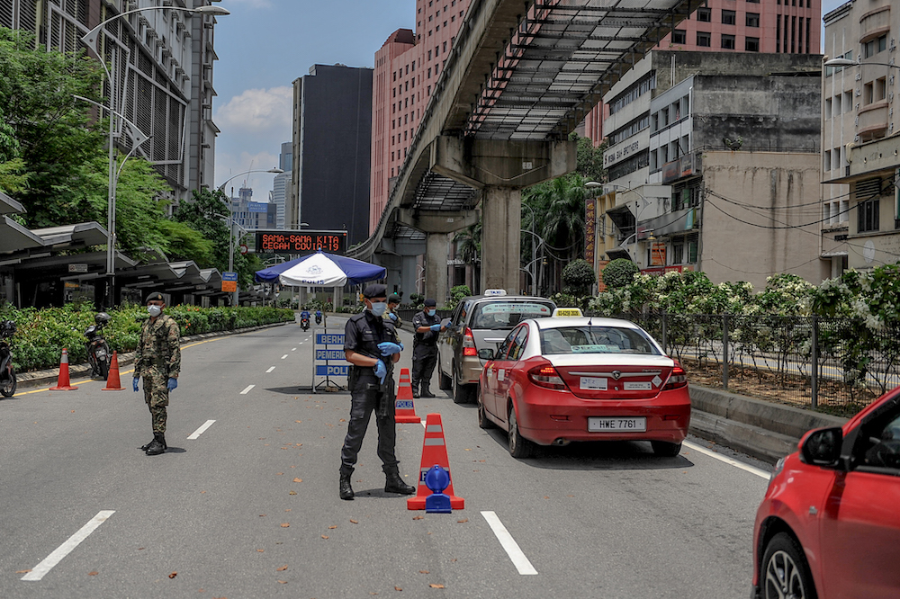 Soldiers and police officers conducting checks at a roadblock during the movement control order (MCO) in Kuala Lumpur March 29, 2020. — Picture by Firdaus Latif