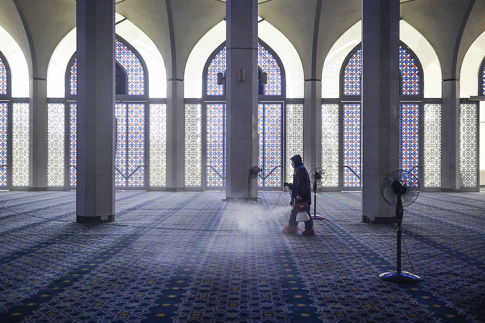 A worker sprays disinfectant in a mosque as a precaution against the spread of Covid-19, Shah Alam March 29, 2020. — Picture by Miera Zulyana