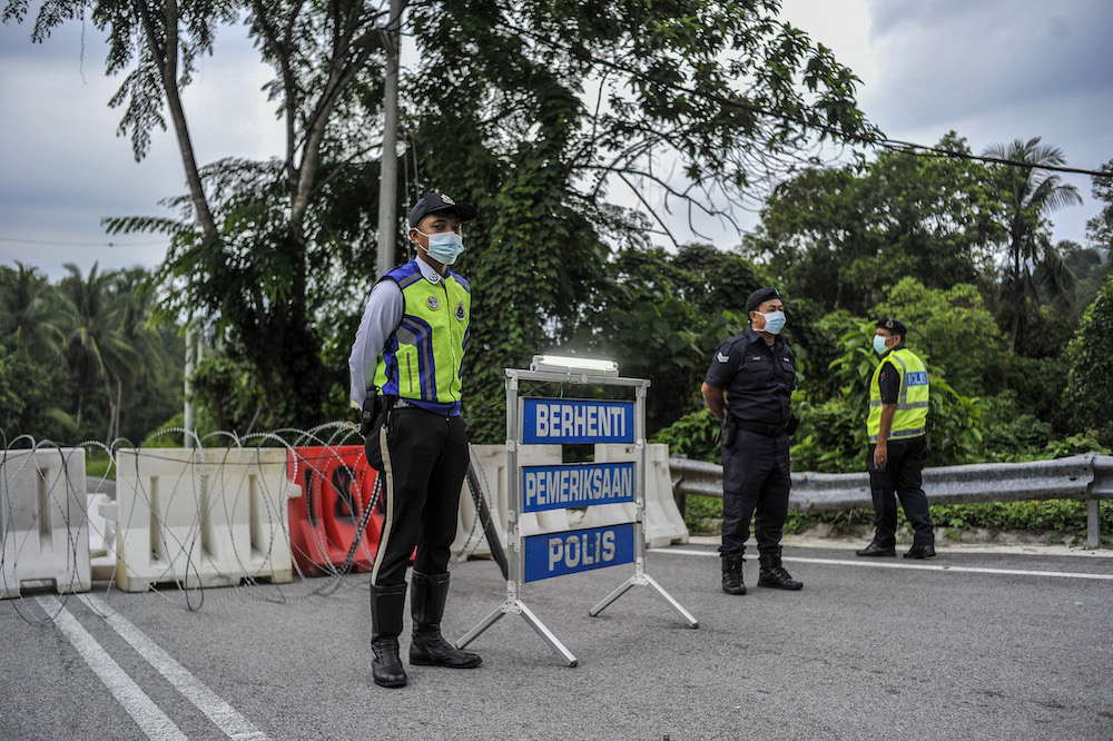 Police officers conducting checks at a roadblock during the enhanced movement control order (EMCO) in seven villages in Hulu Langat March 30, 2020. — Picture by Shafwan Zaidon