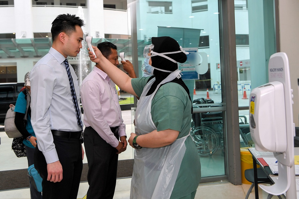 A hospital staff takes the temperature of visitors arriving at the Pantai Hospital in Kuala lumpur March 3, 2020. — Bernama pic