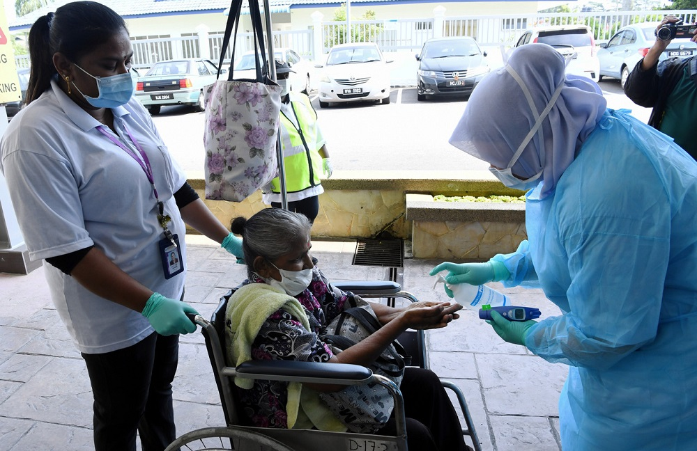A health worker at Mawar Medical Centre provides hand sanitiser to a wheelchair-bound elderly woman in Seremban March 20, 2020. — Bernama pic