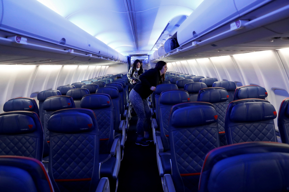 Air travellers grab carry-on luggage behind rows of empty seats aboard a Delta flight, as coronavirus disease disruption continues across the global industry, from New York's JFK International Airport to San Francisco, California, US, March 17, 2020. — Reuters pic