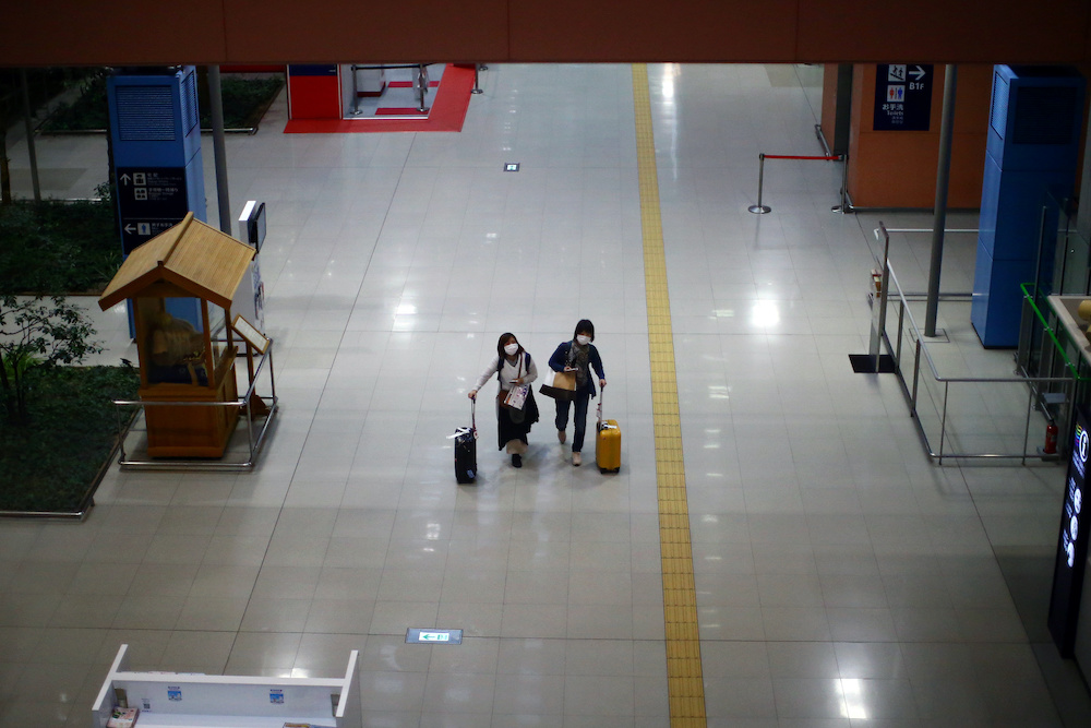 Passengers, wearing protective masks following an outbreak of the coronavirus disease, walk at the almost empty Kansai International Airport in Osaka March 14, 2020. — Reuters pic