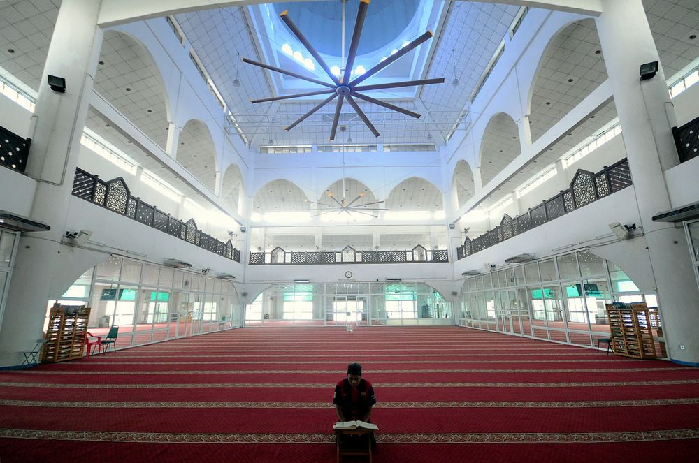 A mosque official reading the Quran while awaiting the time for Asar prayer at the Al-Munawwarah Mosque in Shah Alam , March 15, 2020. — Bernama pic