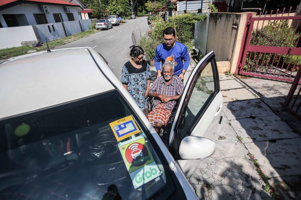 Former Kosmo! Perak bureau chief Mohamad Tarmize Mohd Nor (in blue) helps Vanaja Suppiah (left) wheel her husband to their ride in Ipoh March 26, 2020. — Picture by Farhan Najib