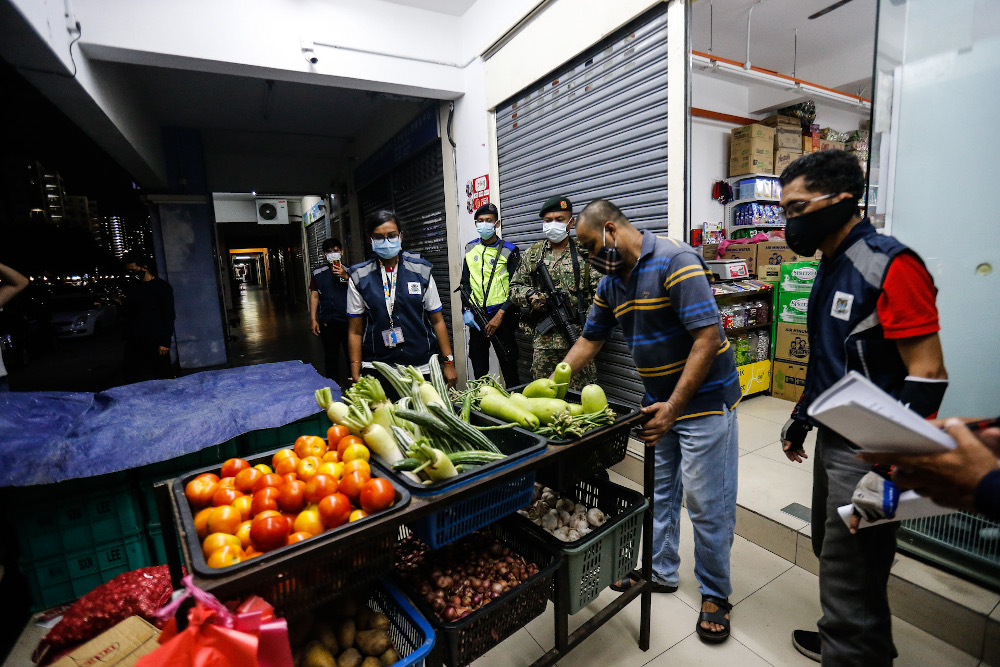 Penang Island City Council enforcement officers, together with Armed Forces and police personnel, conduct spot checks on shops in George Town March 25, 2020. — Picture by Sayuti Zainudin