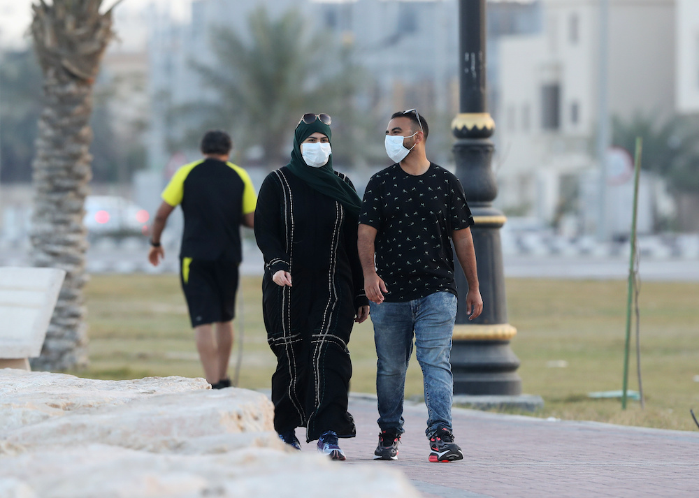 A couple wear a protective face mask, as they walk, after Saudi Arabia imposed a temporary lockdown on the province of Qatif, following the spread of coronavirus, in Qatif, Saudi Arabia March 10, 2020. — Reuters pic