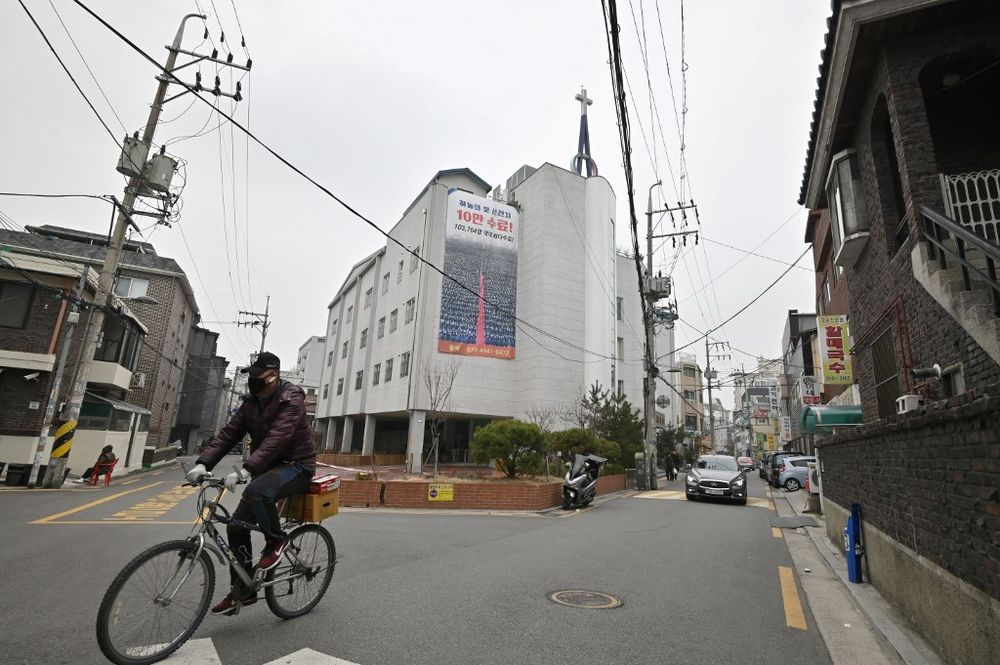 A man wearing a face mask rides a bicycle in front of a branch of the Shincheonji Church of Jesus, which is temporarily closed by the government to help prevent the spread of the COVID-19 coronavirus, in Seoul on March 1, 2020. — AFP pic