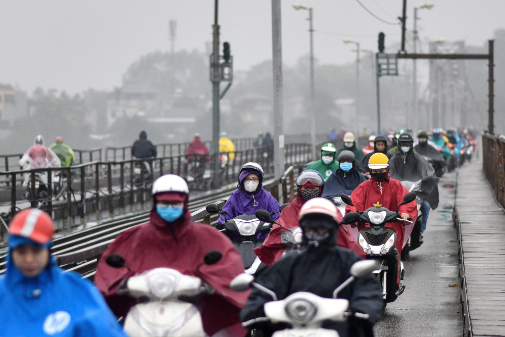 Motorists, wearing facemasks as a preventive measure against the Covid-19 novel coronavirus, ride on a bridge in Hanoi March 17, 2020. — AFP pic