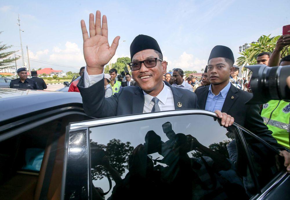Datuk Seri Ahmad Faizal Azumu waves to reporters as he leaves Istana Kinta March 10, 2020. — Picture by Farhan Najib