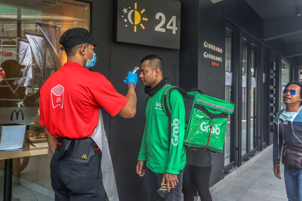 A GrabFood rider is screened by a McDonald's staff in Bukit Bintang as the movement control order kicks in on March 18, 2020. — Picture by Firdaus Latif