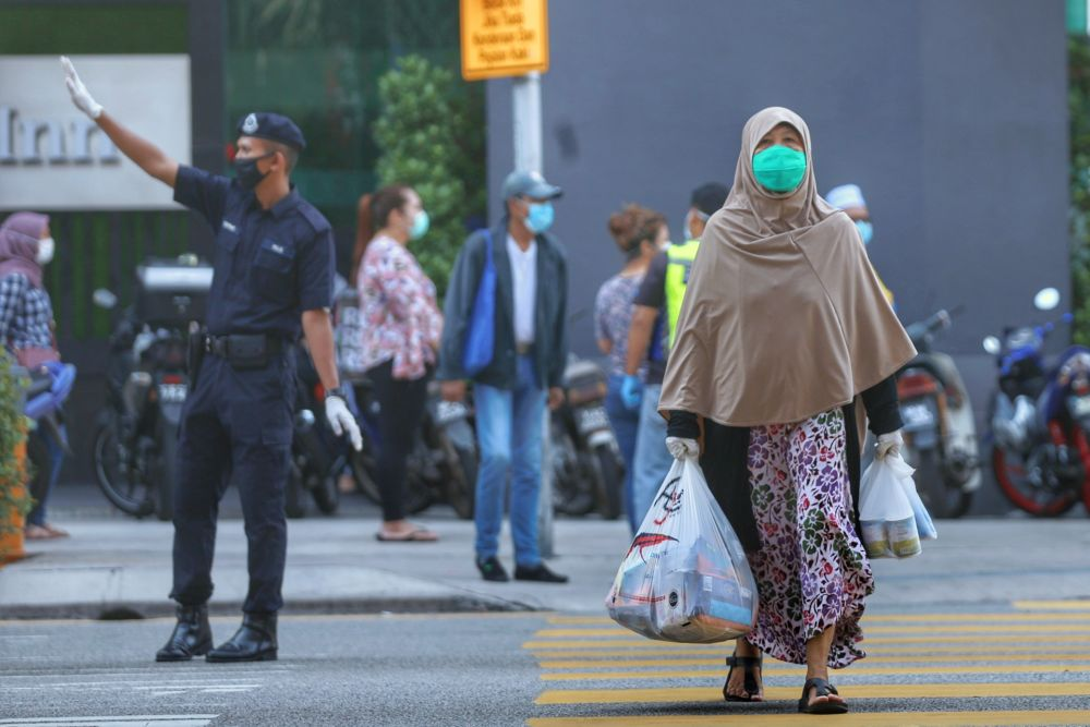 A shopper makes her way out of the Chow Kit wet market with her groceries in Kuala Lumpur March 27, 2020. ― Picture by Ahmad Zamzahuri