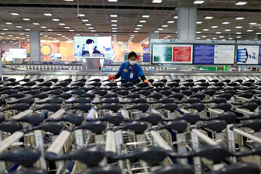 An airport staff member wears a protective mask due to the coronavirus outbreak as she sanitises rows of luggage carts at Suvarnabhumi Airport in Bangkok March 12, 2020. — Reuters pic