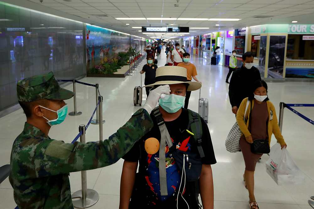 A passenger has his temperature checked due to the Covid-19 outbreak as he arrives at Phuket airport, Thailand March 9, 2020. — Reuters pic