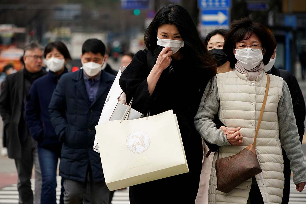 Pedestrians wearing masks to prevent contracting the coronavirus walk on a zebra crossing in Seoul, South Korea, March 12, 2020. — Reuters pic
