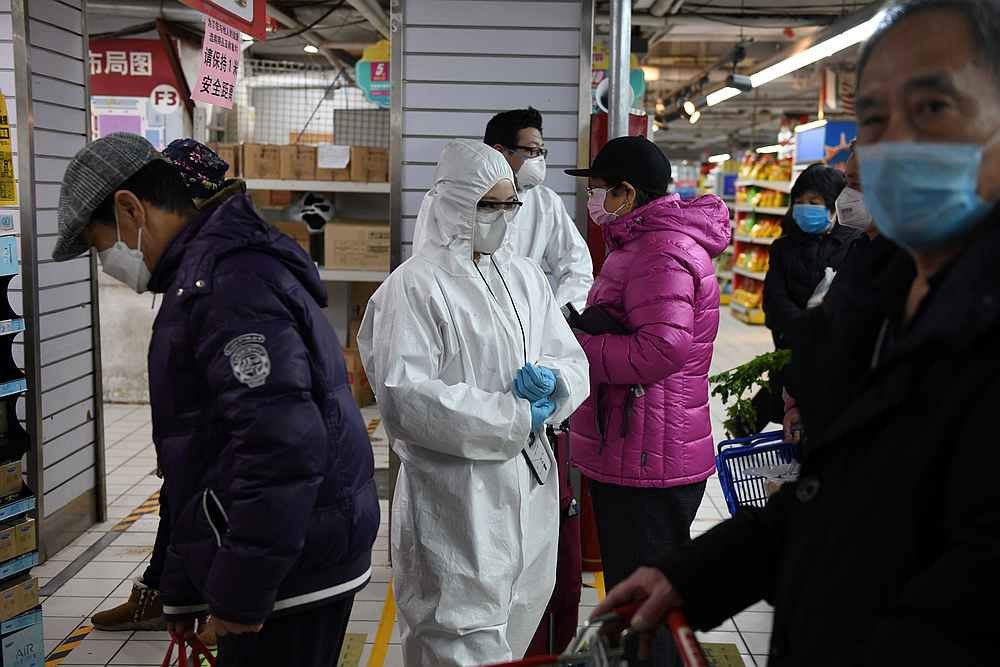 Workers wear protective clothing as a preventive measure against Covid-19 as they monitor customers to make sure they stand one metre apart as they queue in a supermarket in Beijing. — AFP pic